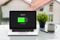 Komputerowy laptop z ładować bateria ekranem na stole w kawiarni zdjęcia stock