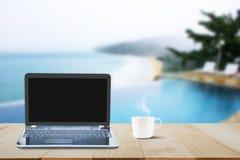 Komputerowy laptop z czerni parawanową, gorącą filiżanką na drewnianym stołowym wierzchołku na zamazanym tle i Fotografia Stock
