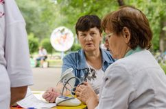 Elderly female volunteer to measure blood pressure in middle-age woman. care about the health stock photo