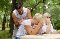 Male volunteer doing back massage to his colleague female volunteer with in the park stock photo