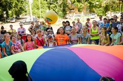 Children throw ball together using multicolored linen. Komsomolsk-on-Amur, Russia - August 1, 2016. Public open Railroader`s day. children throw ball together royalty free stock photography