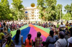 Children throw up ball together using multicolored linen. Komsomolsk-on-Amur, Russia - August 1, 2016. Public open Railroader`s day. children throw up ball stock photography