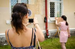 Woman takes picture of her friend getting ready to throw dart at. Komsomolsk-on-Amur, Russia - August 1, 2016. Public open Railroader`s day. woman takes picture stock photos