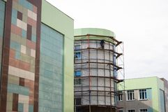 Final part of construction of modern building - glass facade glazing with mirror glass stock photos