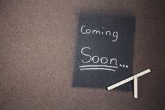 Komst spoedig teken gemaakt krijt op een bord Stock Foto's