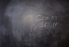Komst spoedig Teksten op Zwart Bord Stock Afbeeldingen