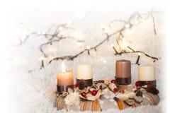 Komstkroon met één brandende kaars en witte achtergrond met Kerstmislichten Royalty-vrije Stock Afbeelding