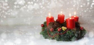 Komstkroon met vier rood brandend kaarsen en Kerstmisdecorum stock afbeelding