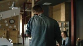 Komt de blonde jonge mens in toevallig op een moderne kantoor of een werkplaats werken terwijl het spreken door zijn mobiele tele stock footage