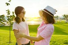 Komunikacja rodzic nastolatek i, nastoletnia dziewczyna opowiada z mamą Tła zielony gazonu, odtwarzania i rozrywki zona, zdjęcia stock