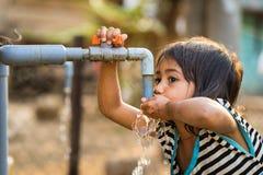 Kon Tum, Вьетнам - 29-ое марта 2016: Вода питья маленькой девочки от внешнего крана который вода поставила путем сверлить хорошо  стоковые фото