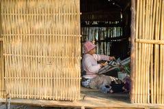 Kon Tum Vietnam - Mars 28, 2016: Den Bahnar kvinnan väver kläder inom av hennes hus i Kon Kotu by, 5km från den Kon Tum staden Arkivbild