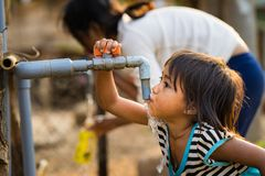 Kon Tum Vietnam - Mars 29, 2016: Lite flickadrinkvatten från det utomhus- klappet som bevattnar levererat av borrande väl i centr royaltyfria bilder