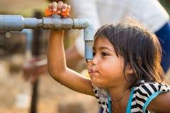Kon Tum Vietnam - Mars 29, 2016: Lite flickadrinkvatten från det utomhus- klappet som bevattnar levererat av borrande väl i centr fotografering för bildbyråer