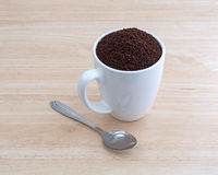 Kona coffee ground beans in a cup with spoon Stock Photo