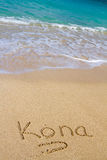 Kona Sand and Water. This vacation image shows the word Kona written in the sand with the Ocean water waves coming in to wash the writing away Royalty Free Stock Photos