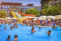 Konakli, Turquía - 18 de agosto de 2017: Piscina con el parque del agua en hotel tropical del centro turístico La nadada feliz de Foto de archivo libre de regalías