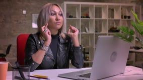 Koncentrat blondynki śliczna caucasian kobieta ma ona w biurowym palce krzyżujący podczas gdy siedzący samotnie i patrzejący