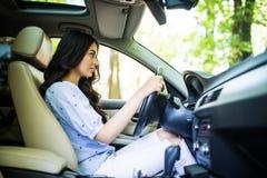 Koncentrat för ung kvinna i en bil på vägen royaltyfria foton