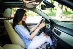 Koncentrat för ung kvinna i en bil på vägen arkivfoton