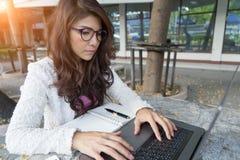 Koncentrat för ung kvinna som arbetar på bärbara datorn asiatisk flicka som lärer royaltyfria foton