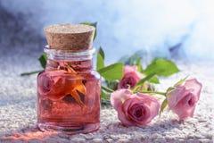 Koncentrat från en ros i en glasflaska som omges av rosor och ett par, brunnsorttillvägagångssätt arkivbild