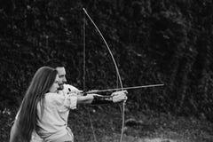 Koncentrat och sikta man och nätt kvinnaskytte med pilbågen och pilen royaltyfri bild