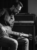 Koncentrera på hans spela för elektrisk gitarr Arkivbilder