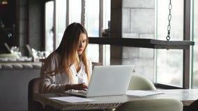 Koncentrerad affärskvinna som arbetar på en bärbar dator i ett kafé nära fönstret arkivfilmer