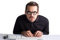 Koncentrerad affärsman med exponeringsglas som skriver på tangentbordet Arkivbilder