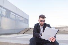 Koncentrerad affärsman som sitter på trappan och ser legitimationshandlingar i hans händer arkivbild