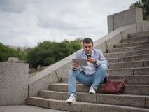 Koncentrerad affärsman som talar på en telefon Arbetare med minnestavlan på en suddig bakgrund Socialt medelbegrepp kopiera avstå arkivbild