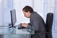 Koncentrerad affärsman som i regeringsställning arbetar på datoren Arkivbild