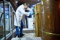 Koncentrerad bryggare som justerar modern utrustning på fabriken arkivfoto