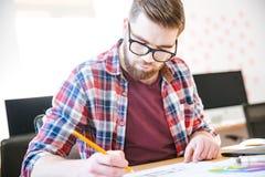 Koncentrerad danande för den unga mannen skissar med blyertspennan Royaltyfria Bilder