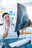 Koncentrerad doktor som analyserar röntgenstrålar Arkivfoto