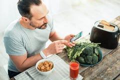 Koncentrerad försiktig man som använder hans mobiltelefon som förbereder sig för att äta Royaltyfri Foto