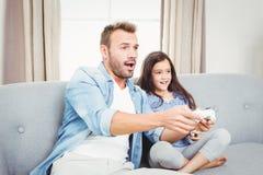 Koncentrerad fader och dotter som spelar videospelet Arkivbilder