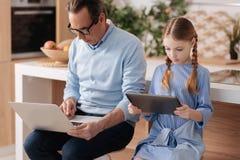 Koncentrerad farfar och sondotter som inomhus använder elektroniska grejer Royaltyfri Foto