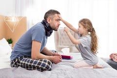 Koncentrerad flicka som behandlar hennes sjuka fader arkivbild