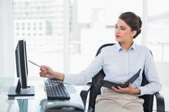 Koncentrerad flott brun haired affärskvinna som kontrollerar hennes dagordning royaltyfria bilder