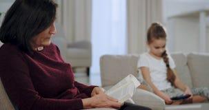 Koncentrerad gammal kvinna läsa en bok medan en liten flicka som sitter på soffan och spelar på en smartphonelek, i lager videofilmer