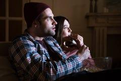 Koncentrerad hållande ögonen på film för par hemma royaltyfria bilder