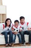 Koncentrerad hållande ögonen på fotbollmatch för familj på tv:n Royaltyfri Fotografi