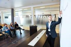 Koncentrerad högtalare som ger presentation i konferenskorridor Royaltyfri Foto