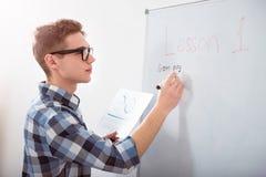 Koncentrerad handstil för manlig student på svart tavla Arkivbild