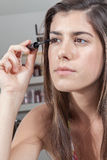 Koncentrerad kvinna som applicerar mascara royaltyfria foton