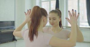 Koncentrerad kvinna som ser reflexion i spegel arkivfilmer