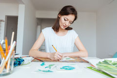 Koncentrerad kvinnamålaredanande skissar med blyertspennan i konststudio Arkivfoto