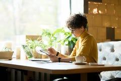 Koncentrerad kvinnavisningrapport i kafé royaltyfri bild